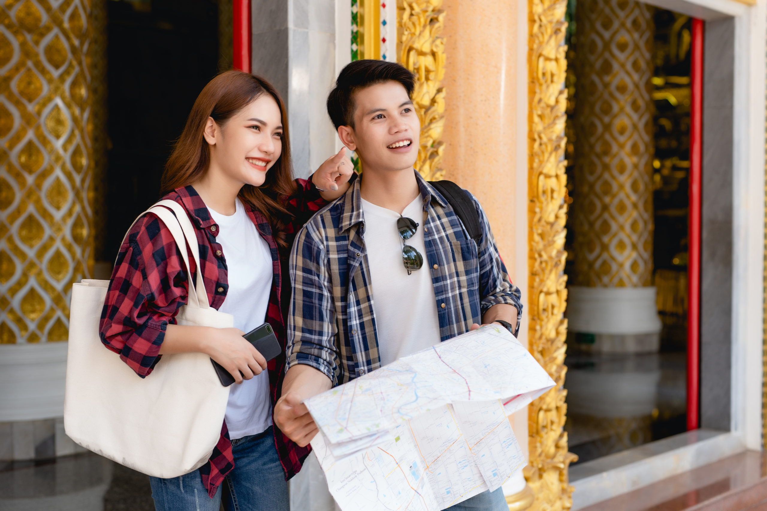 young couple backpackers checking map on paper and smartphone