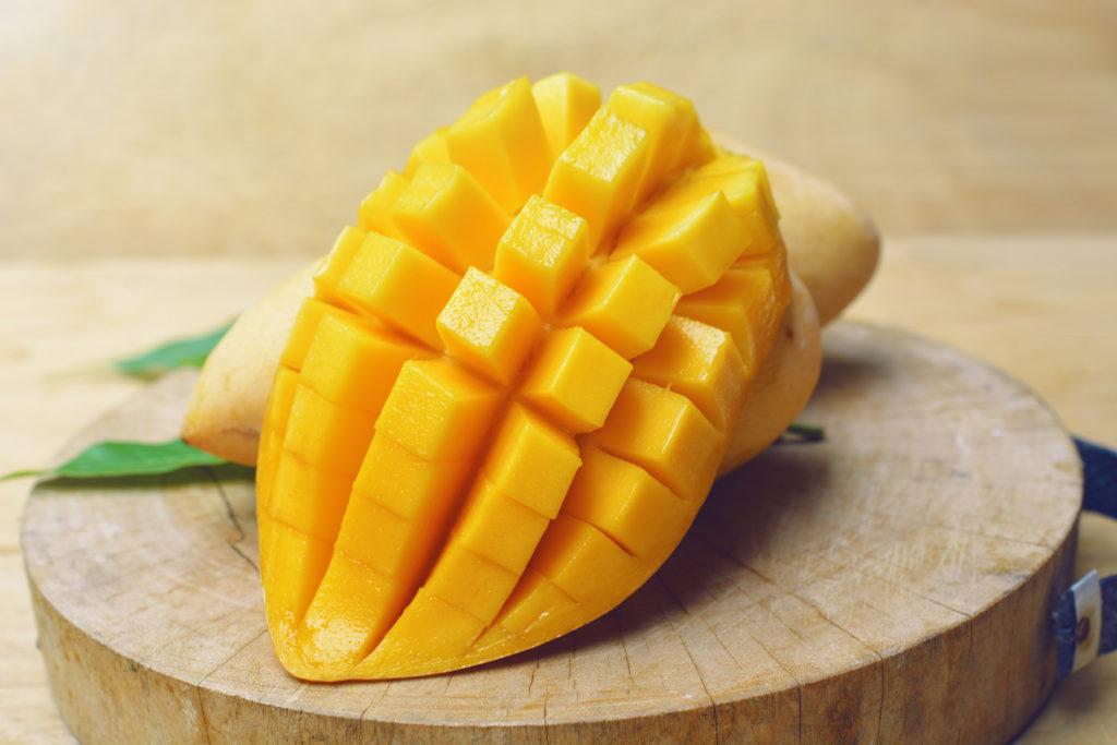mangue mûre avec feuille de mangue sur une planche de bois.