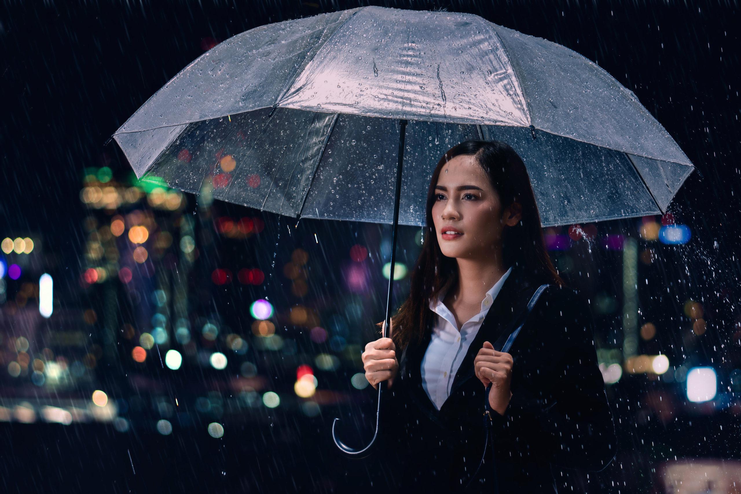 Femme d'affaires avec parapluie sous la pluie.