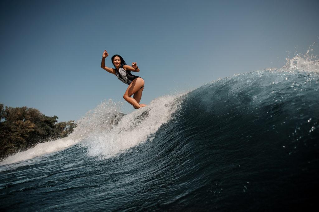femme brune surfant sur une planche de surf dans la mer